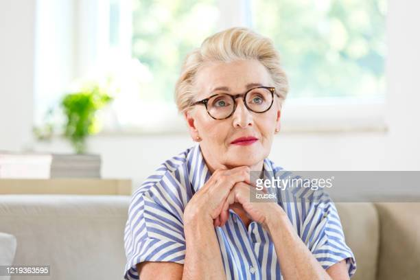 portrait of beautiful elderly lady at home - izusek stock pictures, royalty-free photos & images