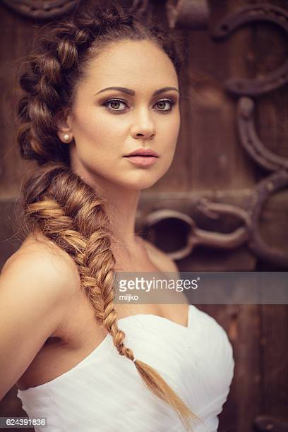 Portrait of beautiful fashion model as a bride posing outdoors
