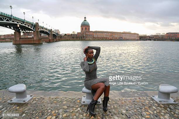 Portrait Of Beautiful Fashion Model Sitting On Bollard By Garonne River In City