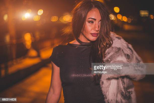 Portrait of beautiful fashionable woman walking on the river jetty at night