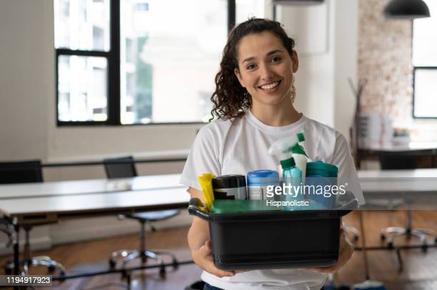 portrait of beautiful female cleaner holding a bucket with cleaning supplies at an office smiling at camera - service occupation stock pictures, royalty-free photos & images