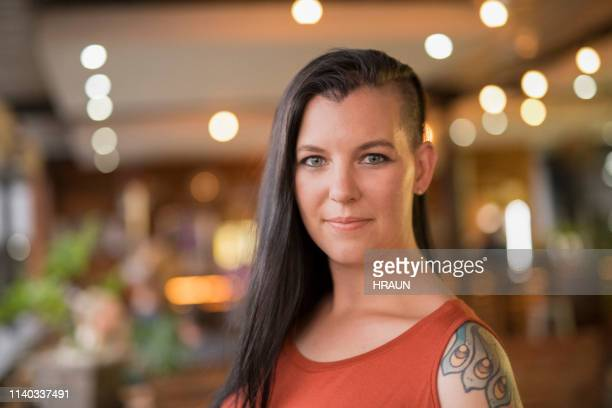 portrait of beautiful female hipster at restaurant - half shaved hairstyle stock pictures, royalty-free photos & images