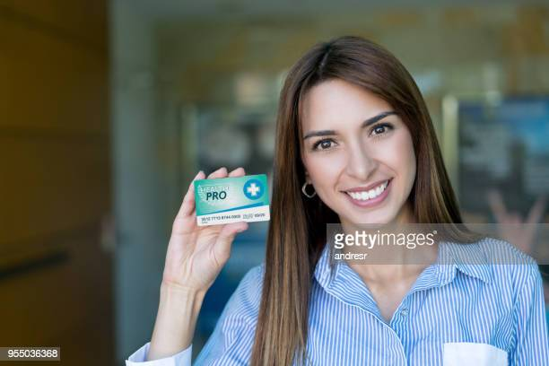 portrait of beautiful female patient holding a medical business card looking at camera smiling - business cards stock photos and pictures