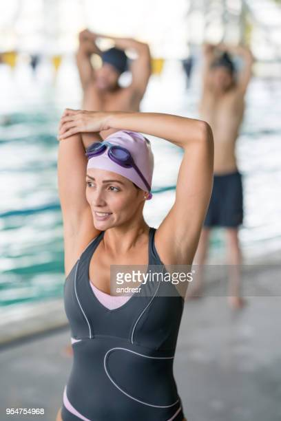 Portrait of beautiful female swimming instructor stretching before going into the pool
