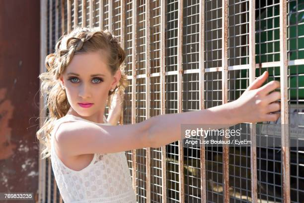 Portrait Of Beautiful Girl Standing By Chainlink Fence