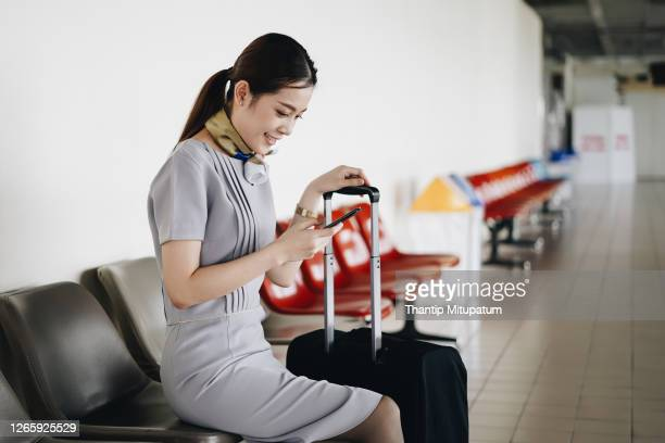 portrait of beautiful hostess in airport with mobile phone. - crew stock pictures, royalty-free photos & images
