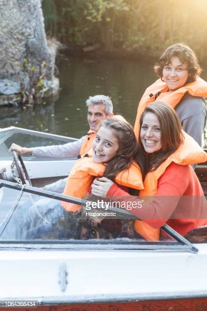 portrait of beautiful latin american family enjoying an afternoon on the boat all looking at camera smiling - life jacket stock pictures, royalty-free photos & images
