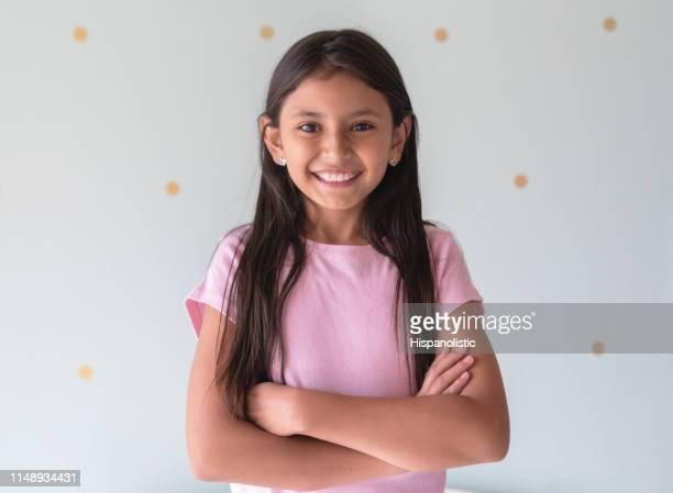 retrato de la hermosa niña latinoamericana frente a la cámara sonriendo con los brazos cruzados - niñas fotografías e imágenes de stock