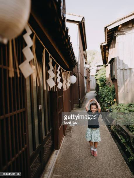 Portrait of beautiful little girl dancing in old Japanese village, Sadoshima