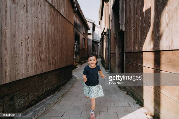 Portrait of beautiful little girl running towards camera with smile, Japan