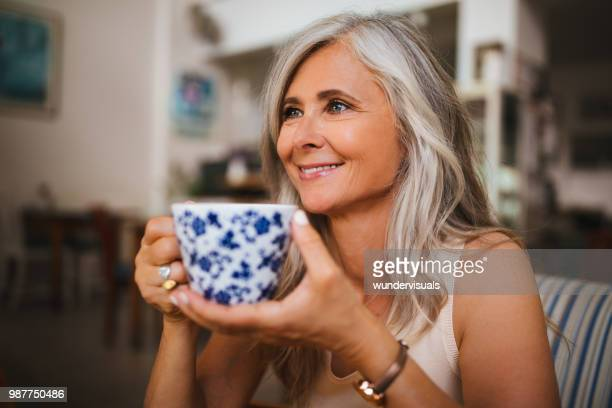portrait of beautiful mature woman drinking tea at coffee shop - grey hair stock pictures, royalty-free photos & images