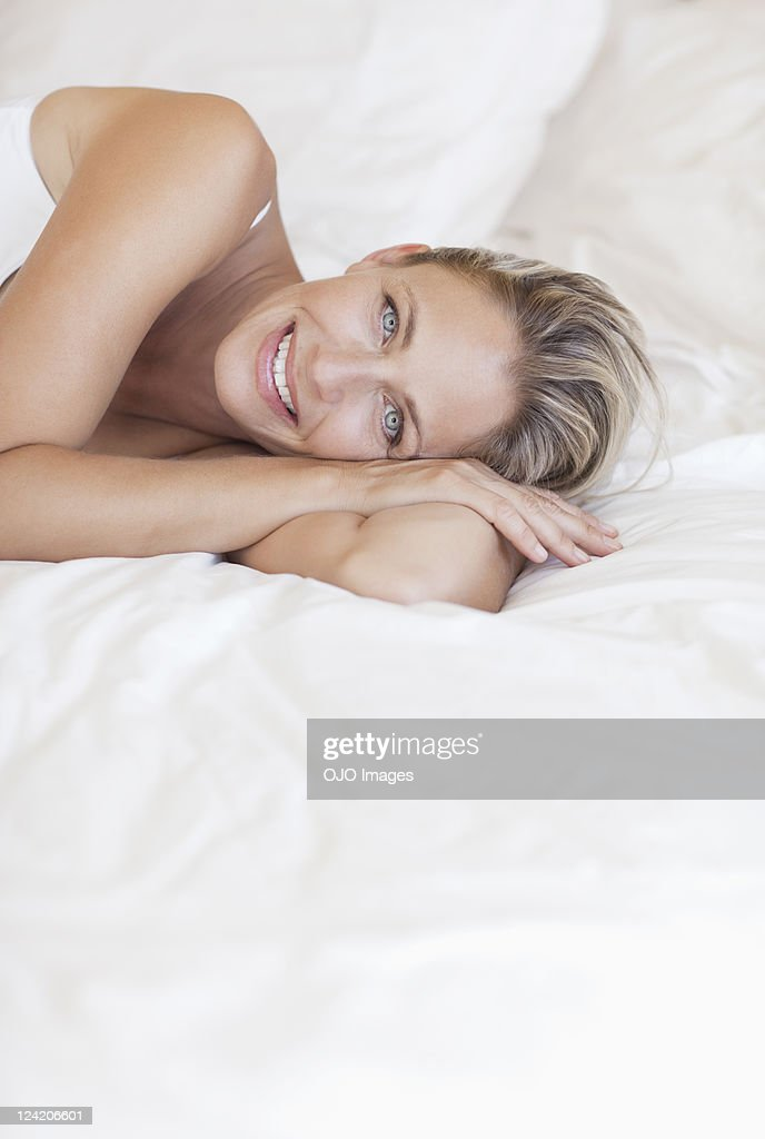 Portrait of beautiful mature woman lying in bed : Stock Photo