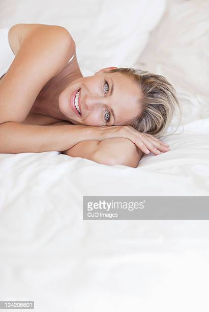 Portrait of beautiful mature woman lying in bed