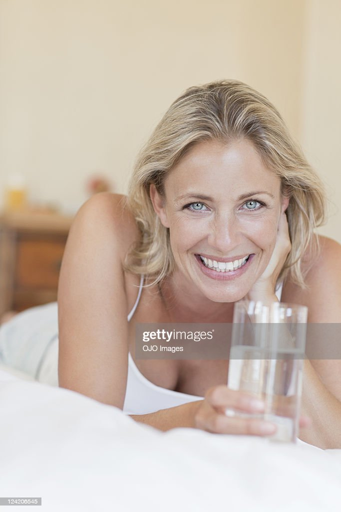 Portrait of beautiful mature woman lying in bed with a glass of water : Stock Photo