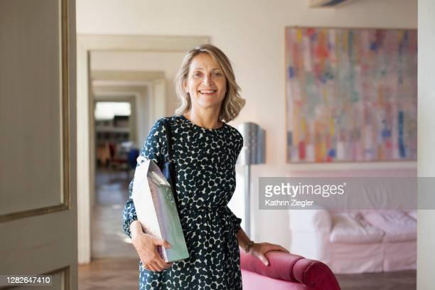 portrait of beautiful mature woman ready to go out, holding a present - une seule femme d'âge mûr photos et images de collection