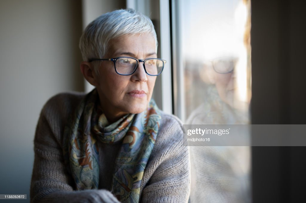 Portrait of beautiful mature woman relaxing by the window : Stock Photo
