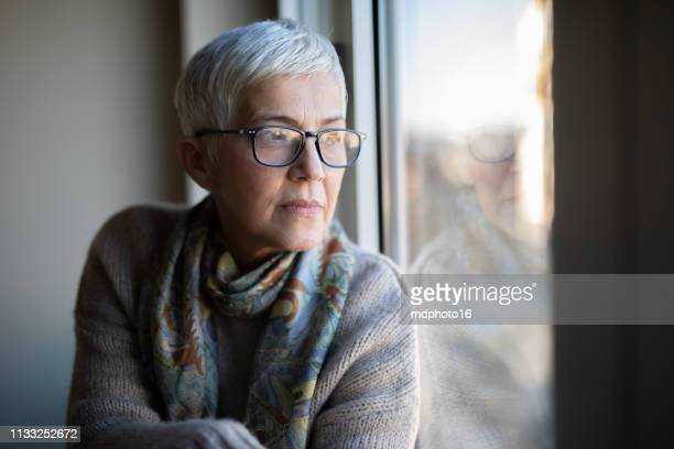 portrait of beautiful mature woman relaxing by the window - looking through window stock pictures, royalty-free photos & images