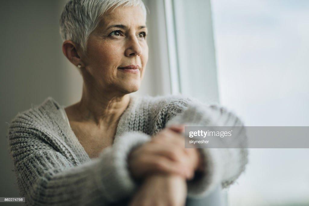 Portret van mooie rijpe vrouw ontspannen bij het raam. : Stockfoto