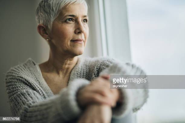 portrait of beautiful mature woman relaxing by the window. - looking through window stock pictures, royalty-free photos & images