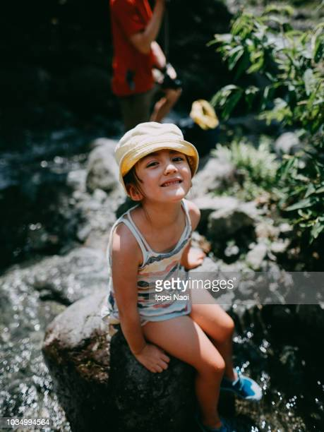 Portrait of beautiful mixed race little girl smiling at camera while having her feet in river water