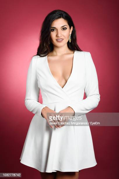portrait of beautiful model wearing white dress against red background - dress cleavage stock pictures, royalty-free photos & images