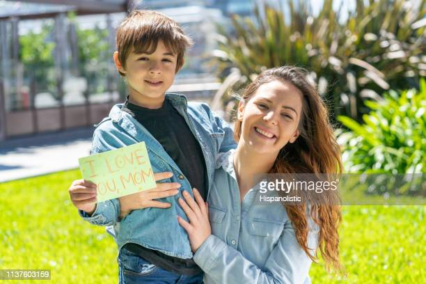 portrait of beautiful mom and son looking at camera smiling while boy holds a card for mother's day - hispanolistic stock photos and pictures