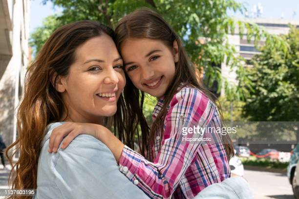 portrait of beautiful mother and daughter leaning their heads together and hugging while facing camera smiling - hispanolistic stock photos and pictures