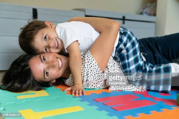 portrait of beautiful mother and loving toddler lying down on her hugging and smiling at camera - hispanolistic stock photos and pictures