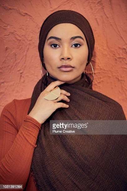 Portrait of beautiful muslim woman against terracotta background