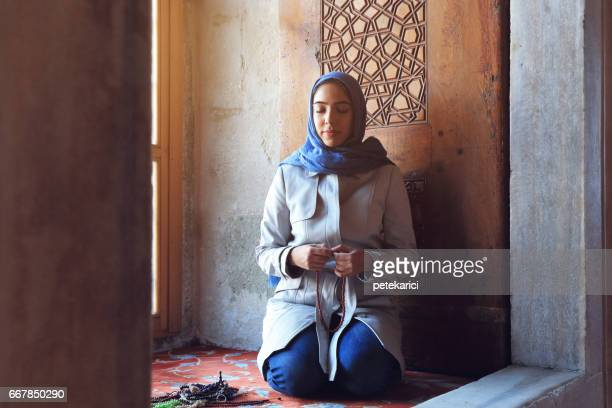 portrait of beautiful muslim woman at prayer in the blue mosque - muslim praying stock pictures, royalty-free photos & images