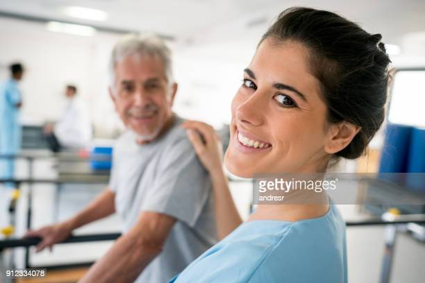 Portrait of beautiful physiotherapist looking at camera smiling while putting her hand on the patients shoulder