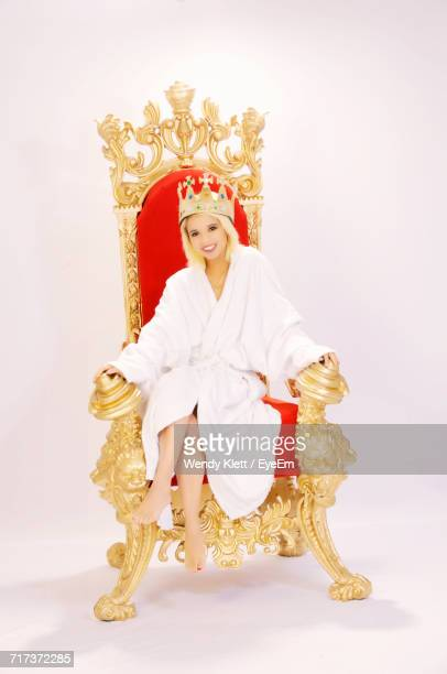 Portrait Of Beautiful Queen Wearing Bathrobe Sitting On Throne Against White Background