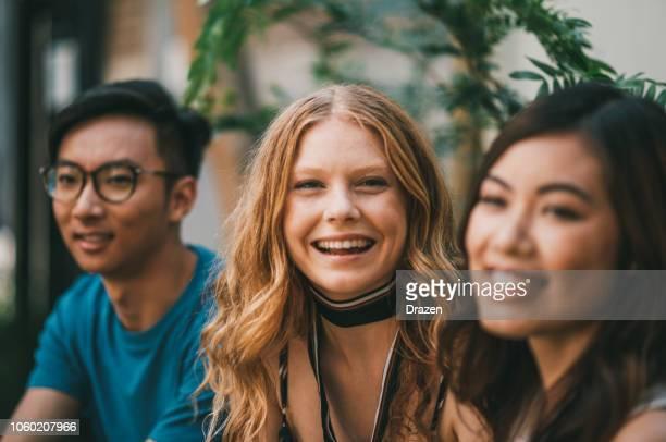 retrato de joven hermosa pelirroja con sus amigos asiáticos - activista fotografías e imágenes de stock