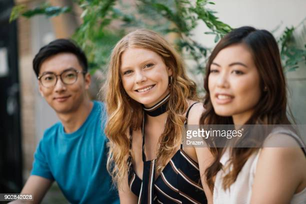 Portrait of beautiful redhead young woman with her Asian friends