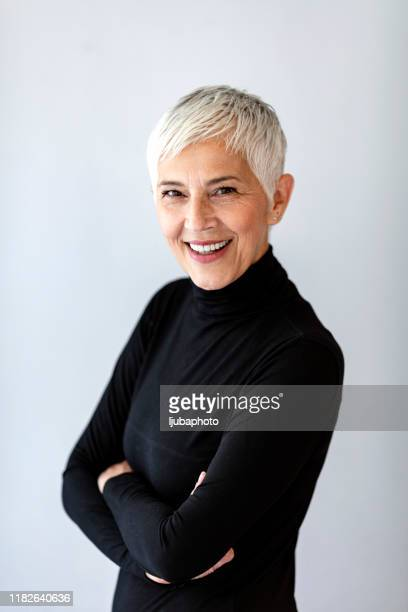 portrait of beautiful senior woman in front of grey wall - white hair stock pictures, royalty-free photos & images