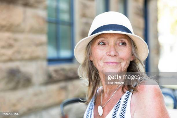 Portrait of beautiful senior woman in summer hat, copy space