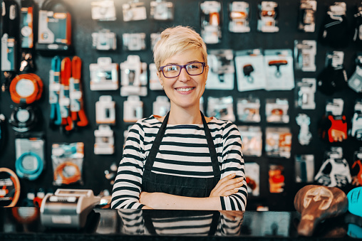 Portrait of beautiful smiling Caucasian female worker with short blonde hair standing in bicycle shop with arms crossed. 1140336148