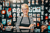 Portrait of beautiful smiling Caucasian female worker with short blonde hair standing in bicycle shop with arms crossed.