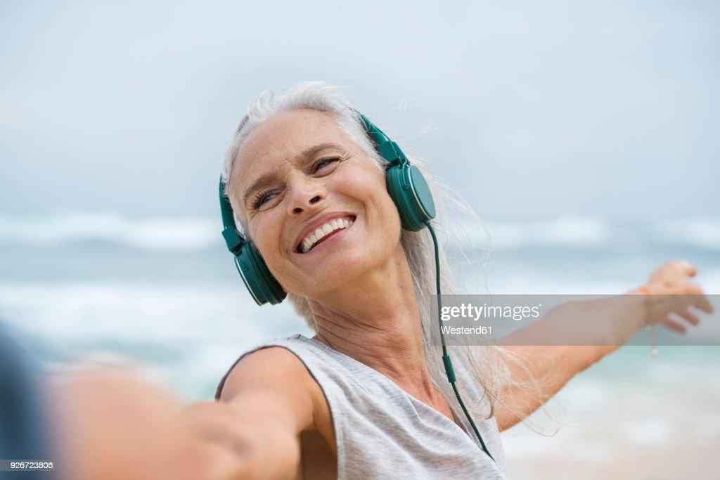 Portrait of beautiful smiling senior woman dancing on beach : Stock Photo