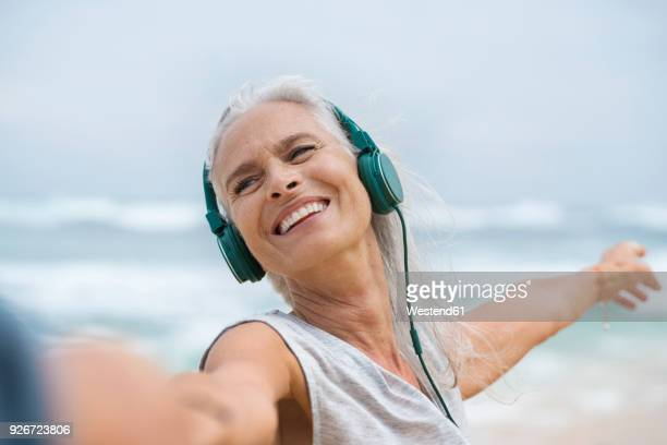 portrait of beautiful smiling senior woman dancing on beach - jung geblieben stock-fotos und bilder