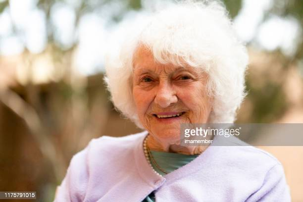 portrait of beautiful smiling senior woman, front view, background with copy space - 90 plus years stock pictures, royalty-free photos & images