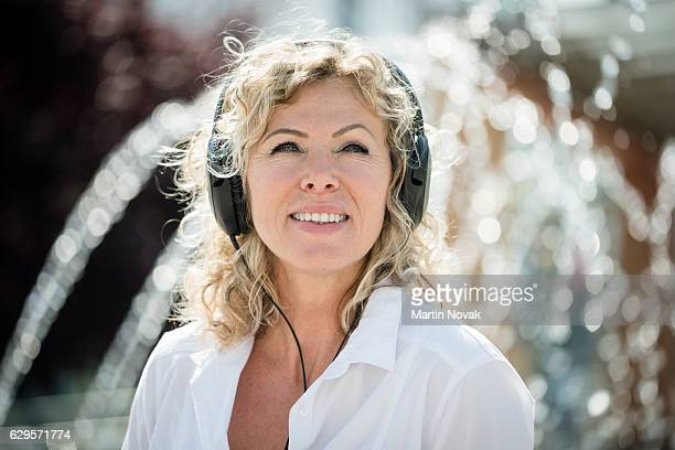 Portrait of beautiful smiling woman enjoying music