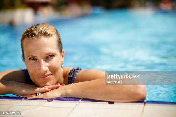 portrait of beautiful smiling woman relaxing in swimming pool - mid adult stock pictures, royalty-free photos & images