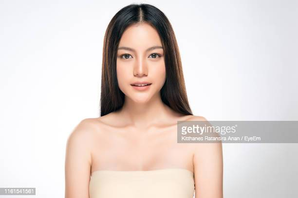 portrait of beautiful woman against white background - frontaal stockfoto's en -beelden