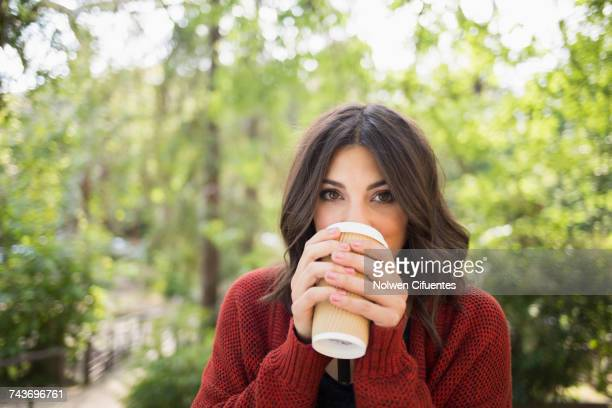 portrait of beautiful woman drinking from disposable glass at park - mid adult woman sweater stock pictures, royalty-free photos & images