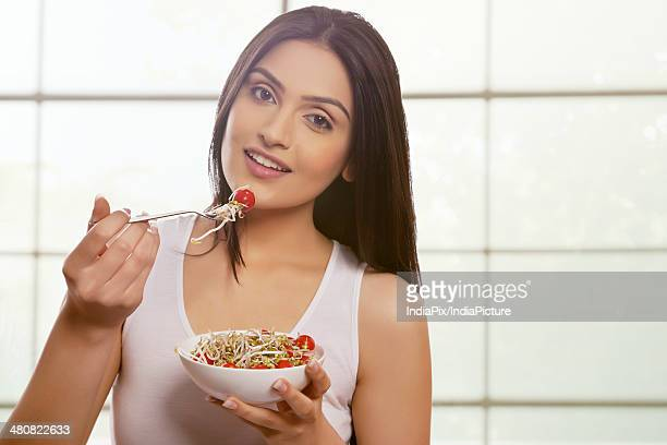 Portrait of beautiful woman eating fresh bean sprouts and cherry tomatoes against window