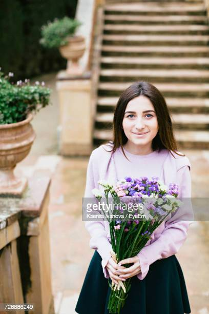 Portrait Of Beautiful Woman Holding Colorful Flowers While Standing Against Steps