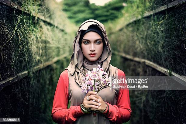 portrait of beautiful woman holding flowers - hijab - fotografias e filmes do acervo