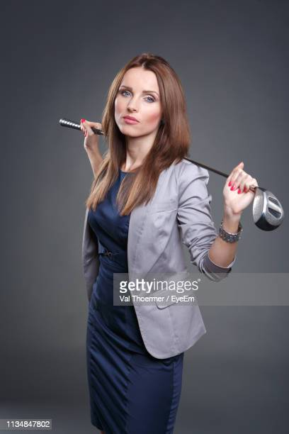 portrait of beautiful woman holding golf club while standing against wall - 女子 ゴルフ ストックフォトと画像