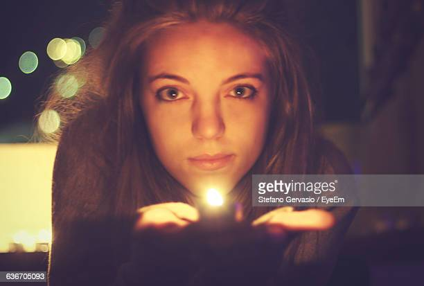 Portrait Of Beautiful Woman Holding Lit Tea Light Candle At Night